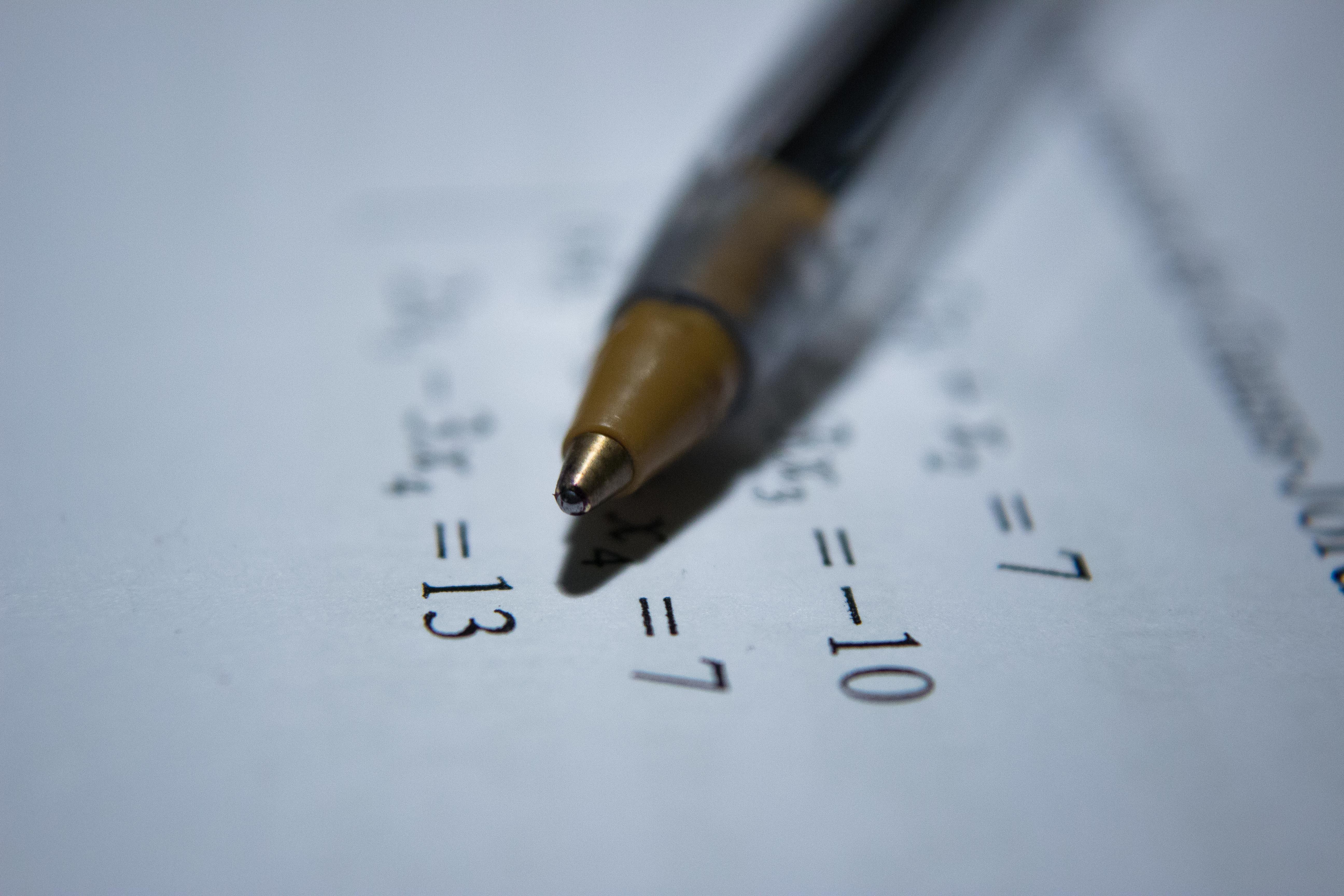 Un stylo bic posé sur une feuille avec des équations mathématique