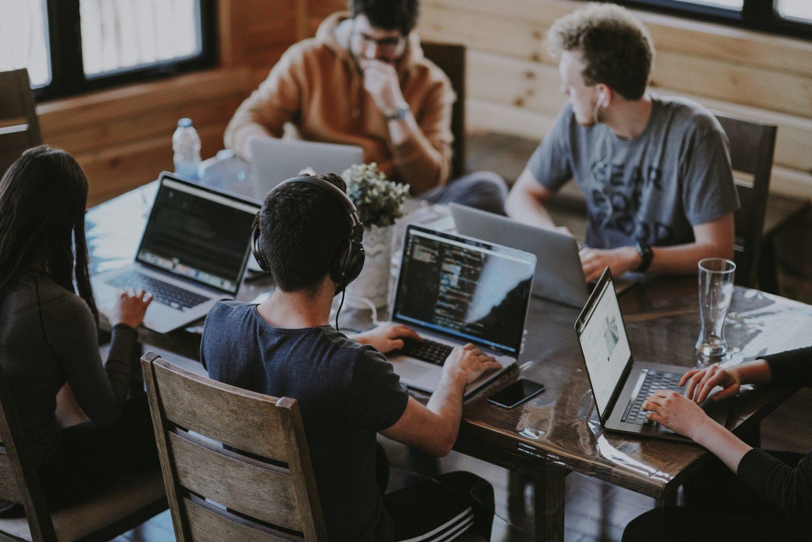 Des gens travaillent sur leur ordinateur et discutent entre eux autour d'une table