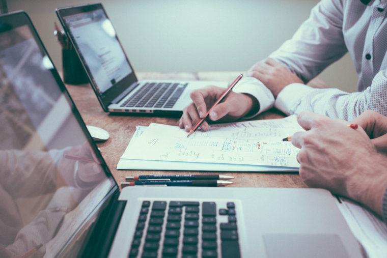 Deux personnes devant des ordinateurs portables et un des deux écrit sur une feuille