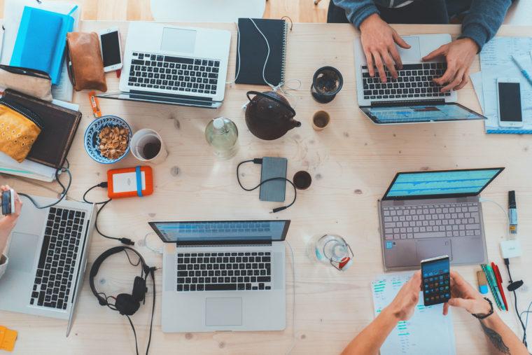 Une table de travail avec cinq ordinateurs portables vue du dessus