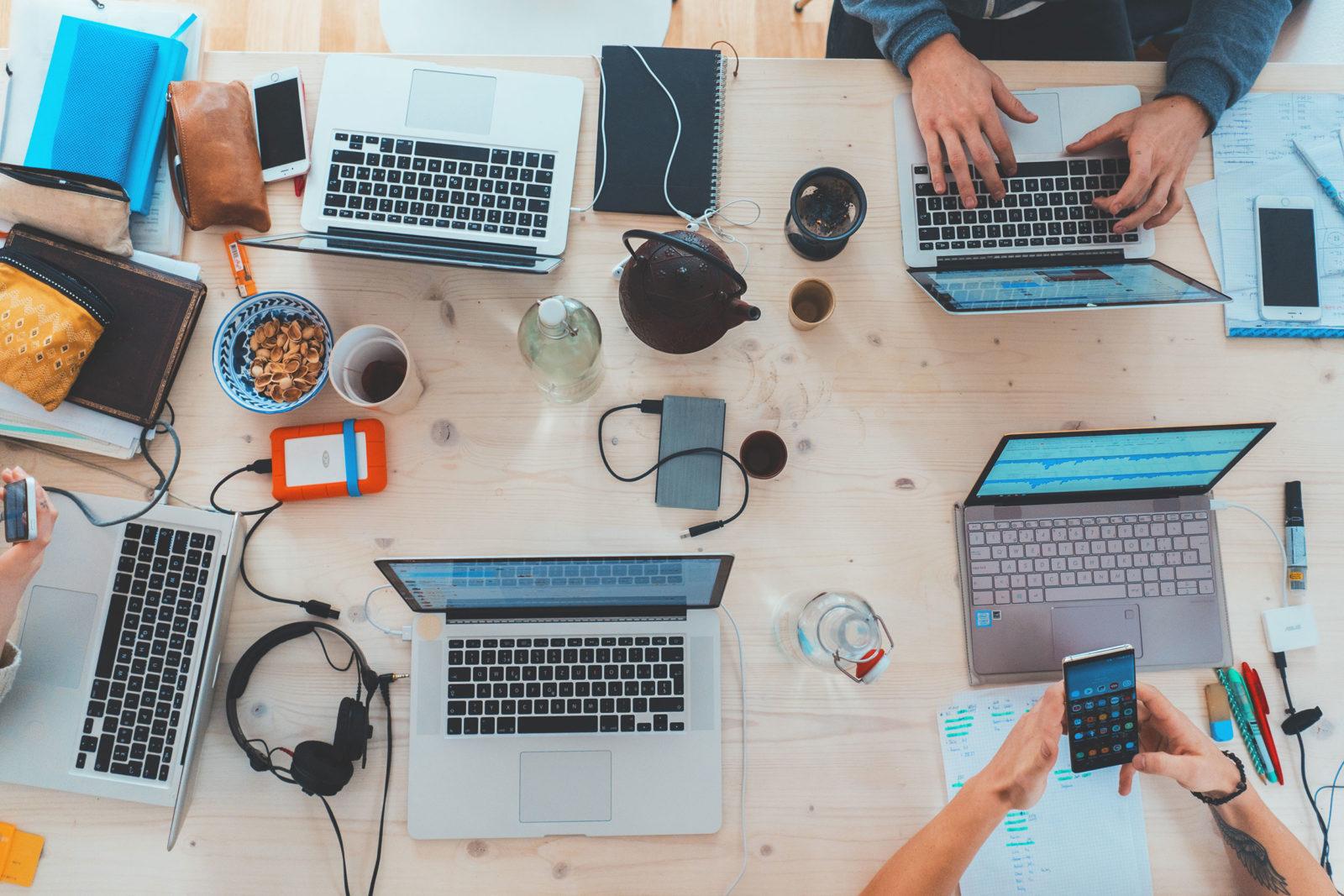 Des gens qui travaillent ensemble sur leur ordinateur autour d'une table