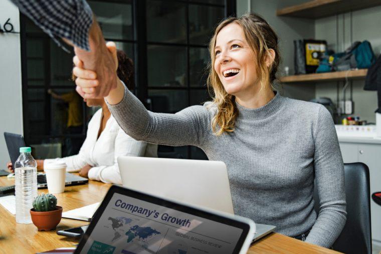 Femme assise à un bureau serrant la main d'un homme