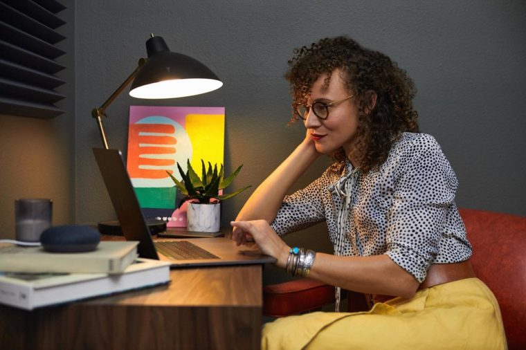 Une femme assise devant un bureau et qui regarde un ordinateur