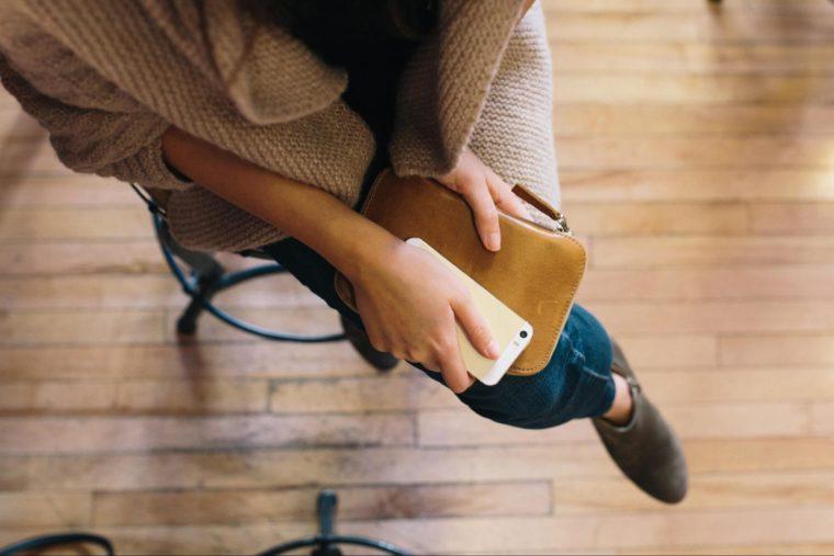 Une femme assise sur un tabouret et qui tient une sacoche dans ses mains