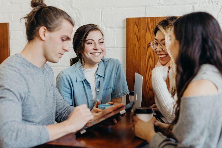 Quatre personnes discutent autour d'une table