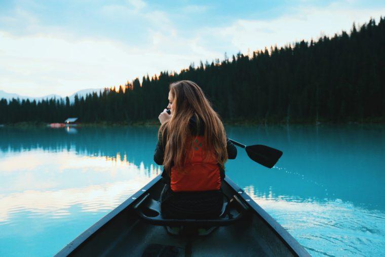 Une femme fait du kayak sur le lac Louise au Canada