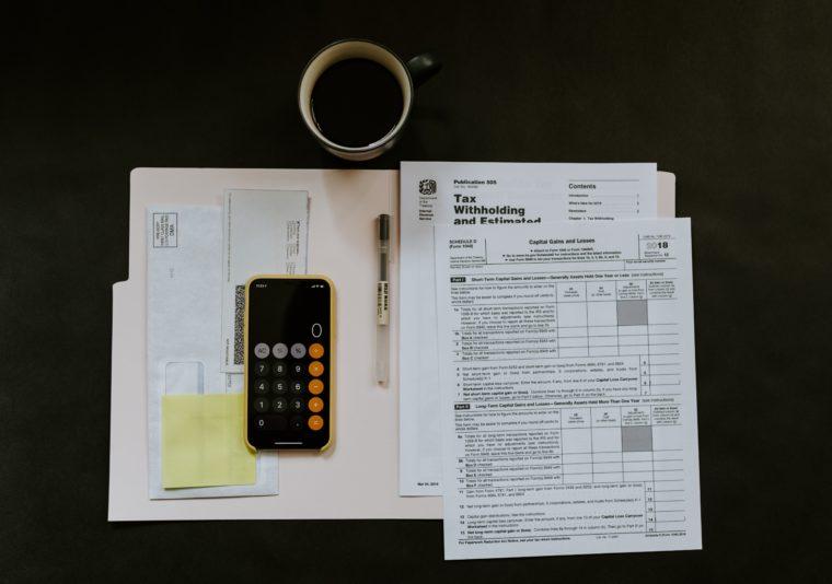Des papiers fiscaux, un café et calculette sur un bureau