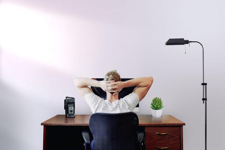 Un homme devant un pc avec les bras derrière la tête