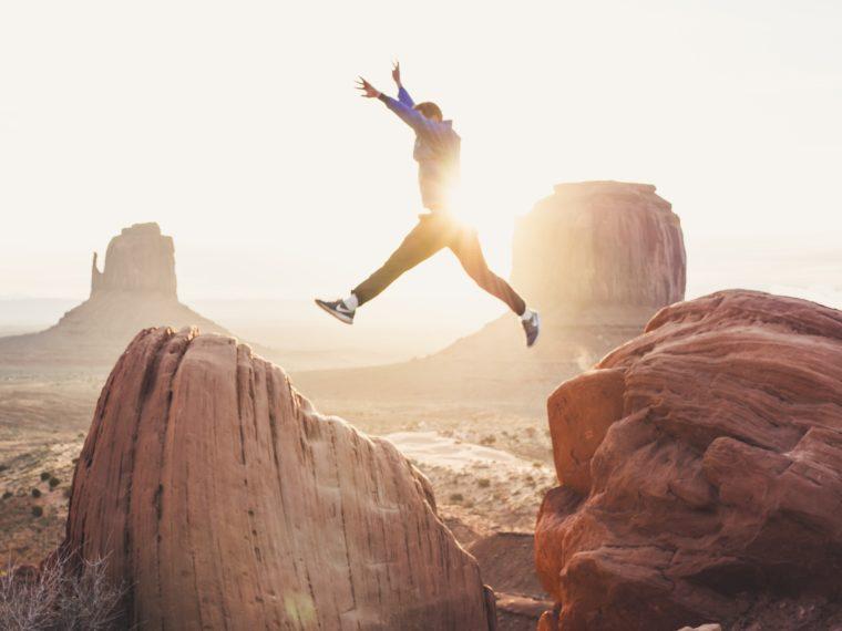 Un homme saute entre deux rochers