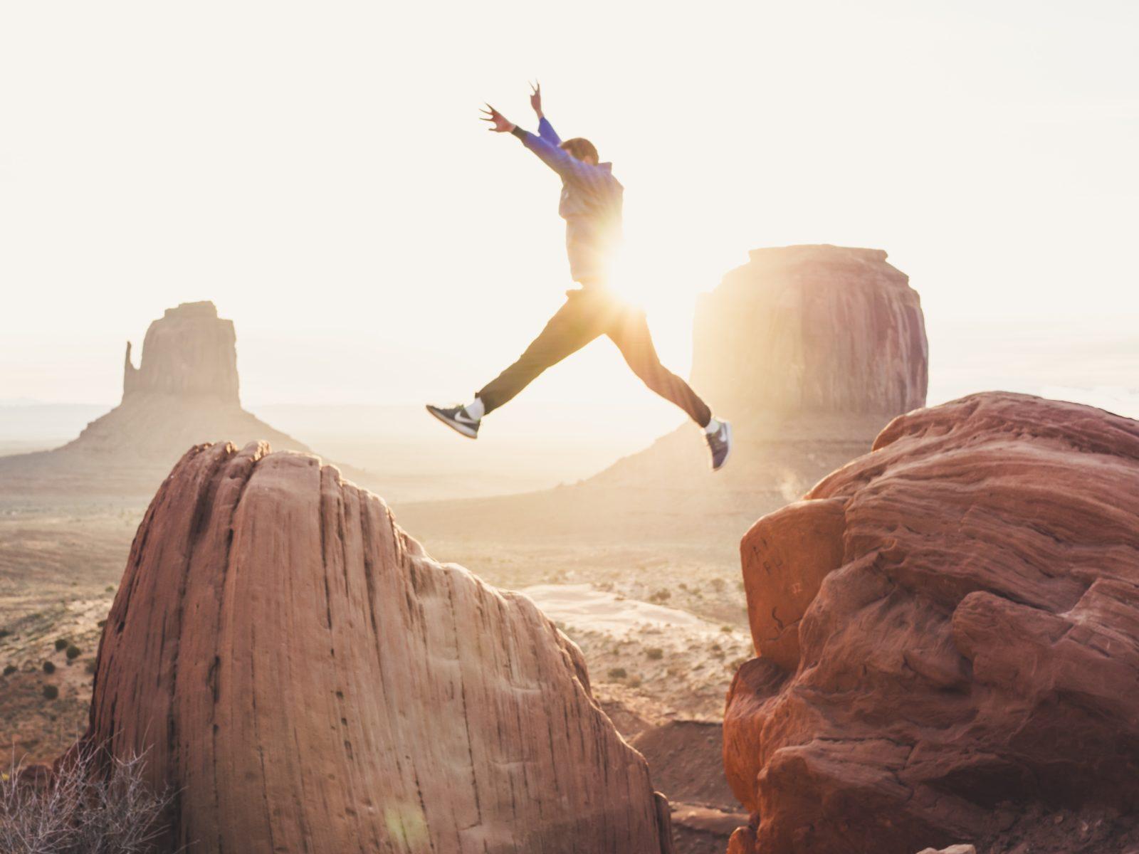 Un homme qui saute entre deux rochers