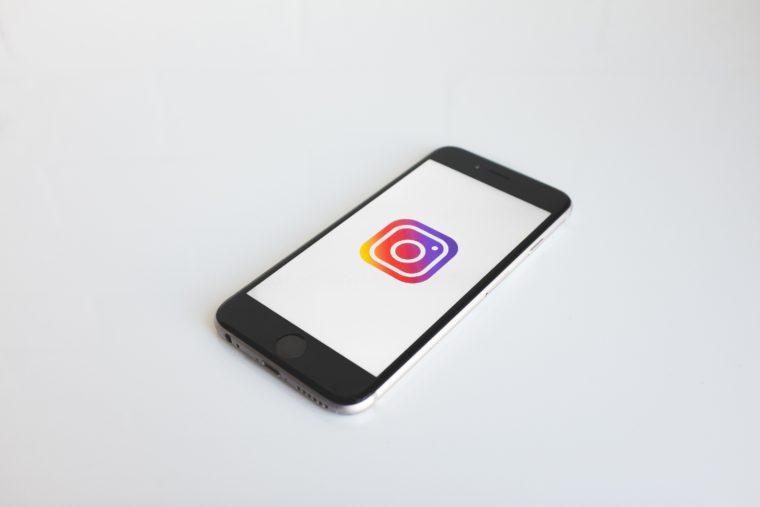 Smartphone posé sur une surface blanche avec le logo d'Instagram affiché sur son écran