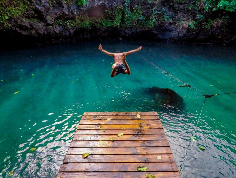 un homme saute dans une eau turquoise depuis un ponton