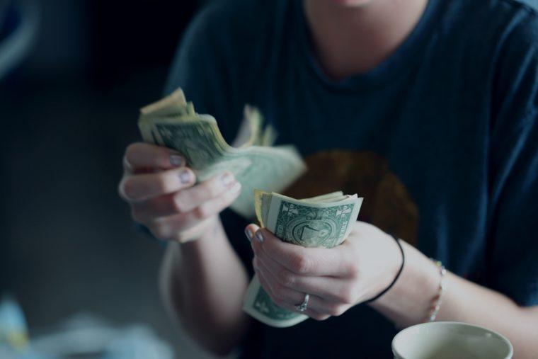Une femme compte des billets de banque