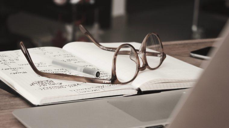 Une paire de lunettes posé sur un cahier de notes