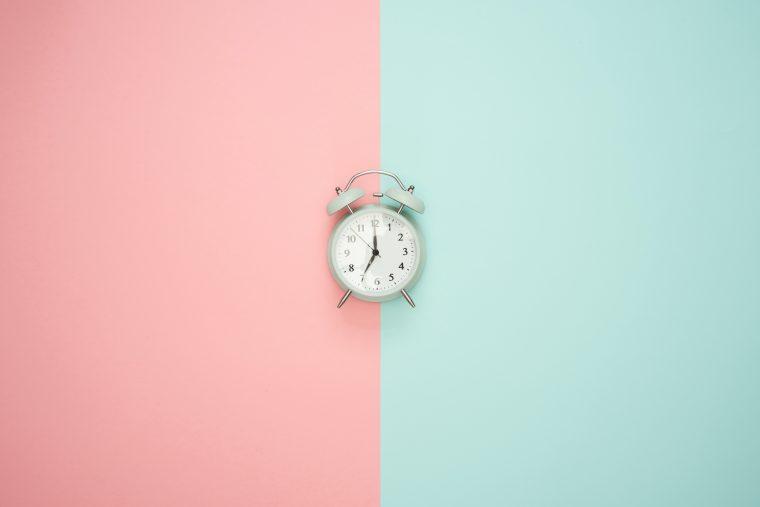 Un réveil blanc sur un fond rose et bleu