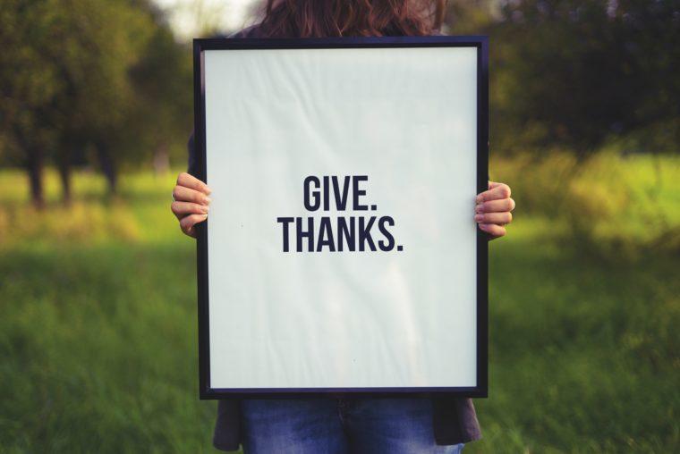 Une femme tient un tableau marqué give thanks